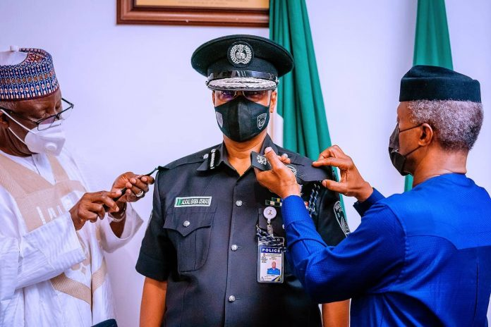 Vice President Yemi Osinbajo SAN decorates the new Acting Inspector General of The Nigeria Police Force Usman Alkali Baba at the State House, Abuja
